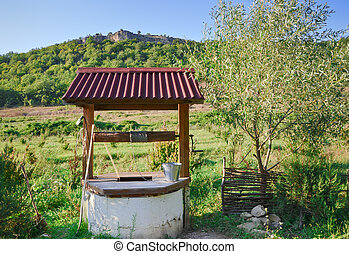 the old well in the countryside against forest