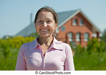 Happy  mature woman  against  home