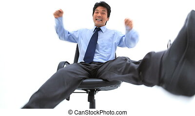 Businessman squirming on his chair against a white...