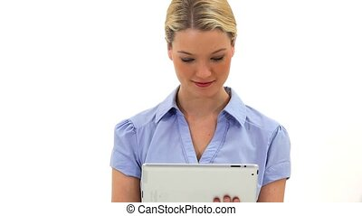 Cheerful blonde woman using a tablet computer against a...