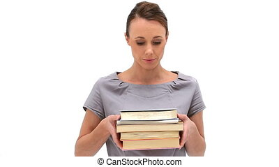 Brunette woman holding books against a white background