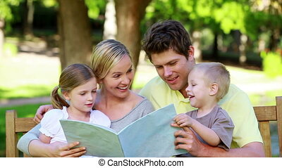 Family looking a picture book on a bench in a park