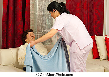 Nurse covering elderly with blanket
