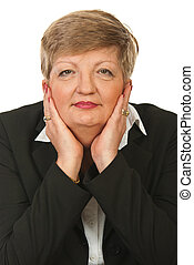 Portrait of mature business woman sitting with hands on face...