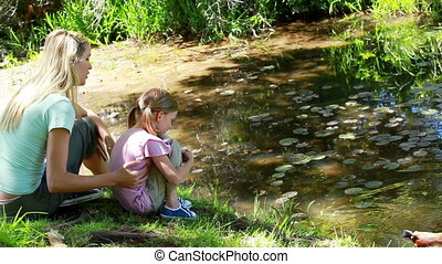 Mother and daughter nourishing a duck