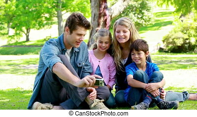 Family watching picture on a digital camera in a park