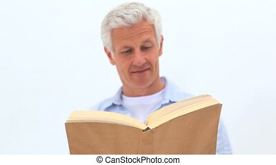 Retired man reading a book against white background