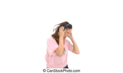Woman with headphones is dancing and jumping