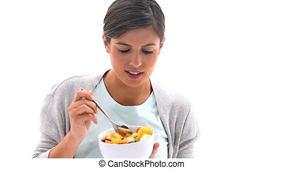 Brunette eating a fruit salad against a white background
