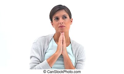 Thoughtful brunette praying against a white background
