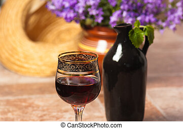 Black jug for wine and a glass of red wine
