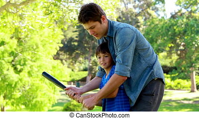 Man practicing baseball with a boy in a park