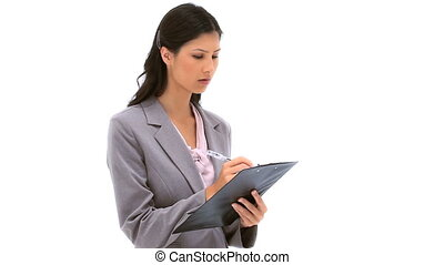 Brunette woman writing on a clipboard against a white...