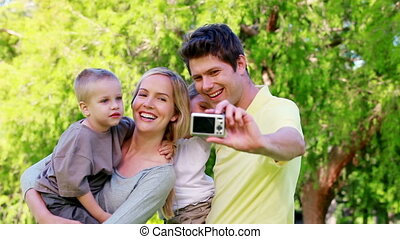 Family taking a picture with a digital camera in a park