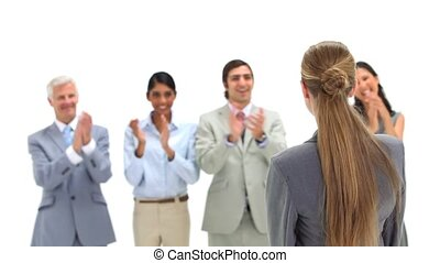 Young businesswoman being congratulated by colleagues...