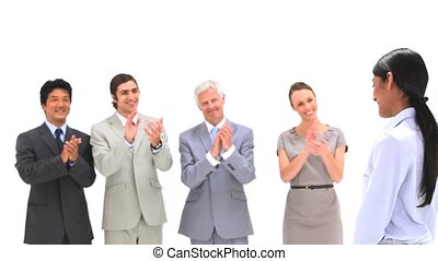 Businesswoman being congratulated by colleagues against a...