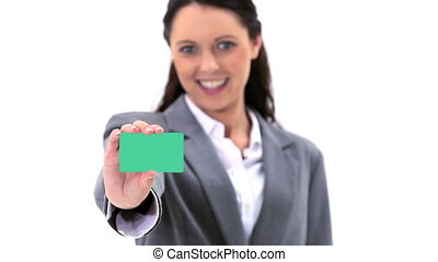 Brunette holding a business card against a white background