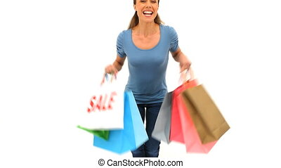 Smiling woman holding shopping bags against a white...