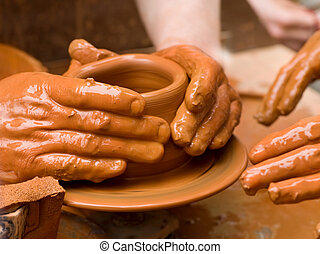 Potter's Hands - Potter shaping a ceramic plate on a pottery...