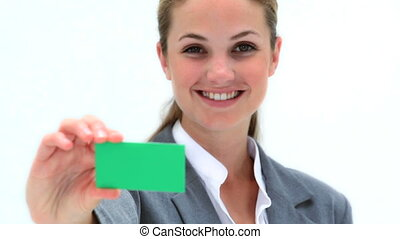 Smiling woman holding a business card against a white...
