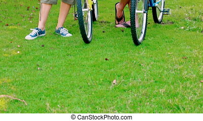 Young couple standing with bikes in a park