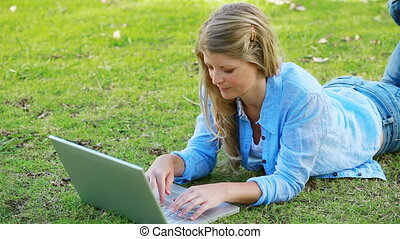 Woman lying while using a laptop