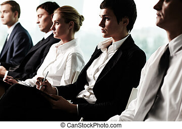 Business seminar - Business people sitting in a row at...