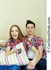 Boring or not - Portrait of young couple during watching TV