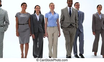 Smiling business people walking against a white background