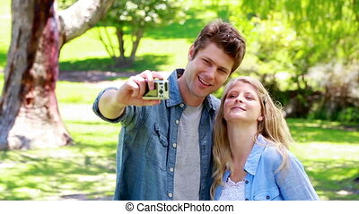 Couple taking a picture together in a park