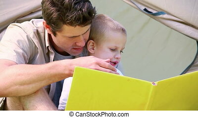Little boy looking picture book with his father with a tent...