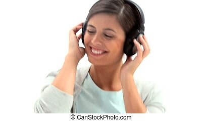 Woman with headphones on is dancing against white background