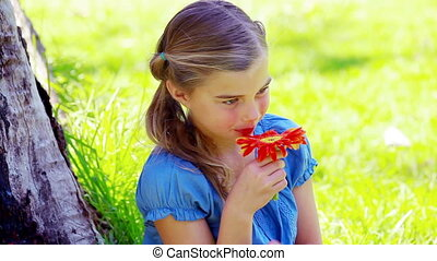 Little girl smelling a flower in a park