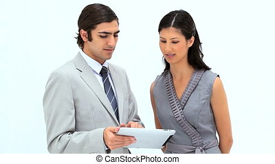 Smiling business people looking at a tablet computer