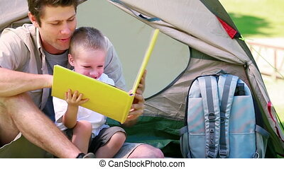 Man with his son looking picture book in front of a tent