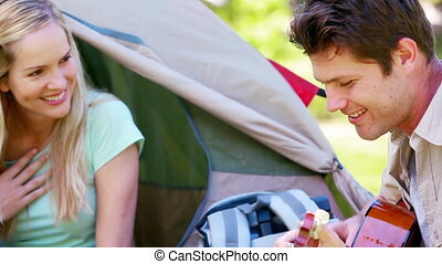 Man playing guitar to his girlfriend while camping