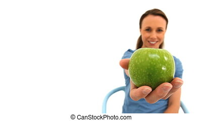 Brunette woman holding a green apple against a white...