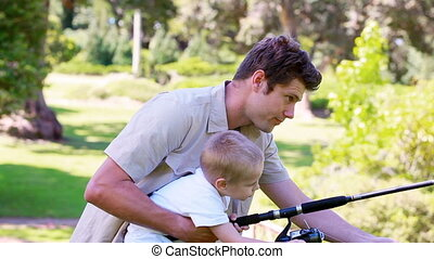 Man fishing with his son in a park