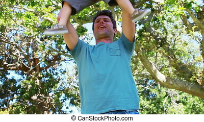 Man putting his son on his shoulders in a park