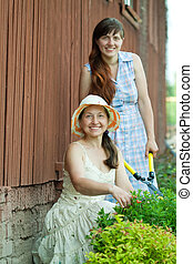 Two women cutting shrubbery at garden
