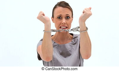 Brunette woman wearing handcuffs against a white background