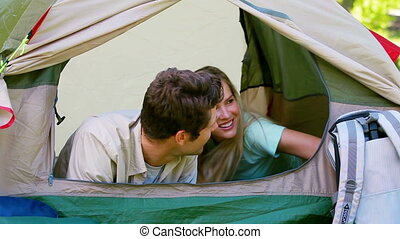 Couple in a tent looking outside in a park