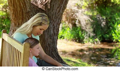 Woman with her daughter on a bench