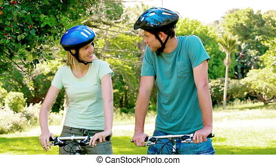 Couple biking with bicycle helmet in a park