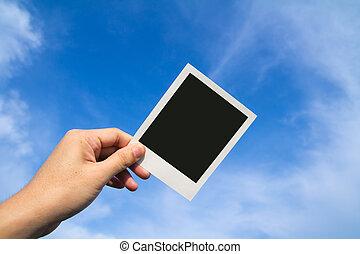 Polaroid photo frames - Hand holds a polaroid photo frame...