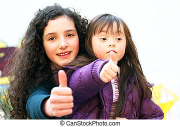 Portrait of beautiful young girls giving thumbs on the...