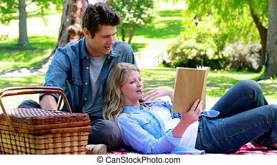 Couple reading a book together in a park