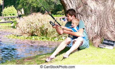 Man teaches to his son fishing in a park
