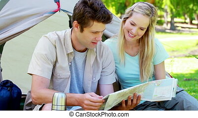 Couple looking a map while camping in a park