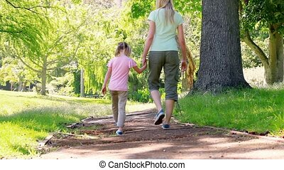 Mother and daughter walking together in a park